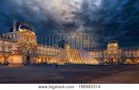 PARIS, FRANCE - DECEMBER 8, 2017: View of famous Louvre Museum with Louvre Pyramid at evening. Louvre Museum is one of the largest and most visited museums worldwide