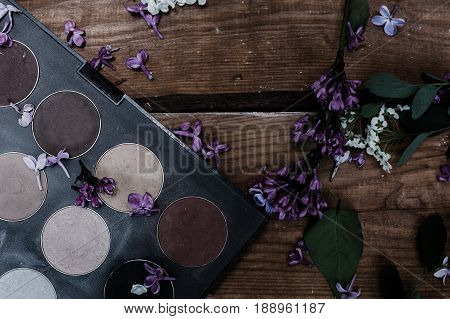 eye shadows. Female cosmetics with flowers in wooden background