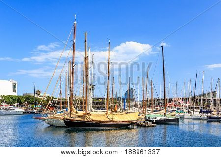 Sailing boats and yachts docked in Port Vell Marina in Barcelona, Catalonia, Spain. Waterfront harbor, famous touristic place at sunny day.