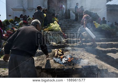 Chichicastenango Guatemala - April 24 2014: Man performing an ancient Maya ritual in the stairs of the Santo Tomas Church (Iglesia de Santo Tomas) in the town of Chichicastenango in Guatemala.
