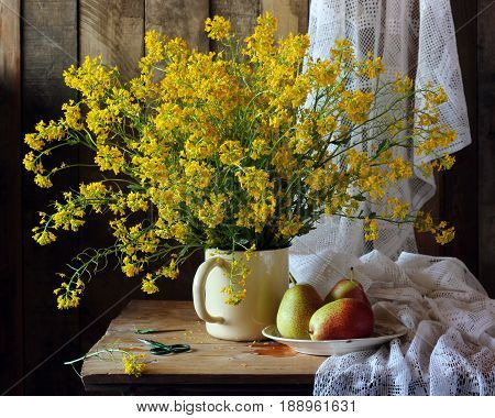 Country still life with a bouquet of yellow wild flowers and pears.