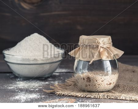 Active rye sourdough starter in glass jar and rye flour on brown wooden background. Starter for sourdough bread. Toned image. Copy space.