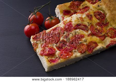 white pizza with tomatoes on the slate stone background