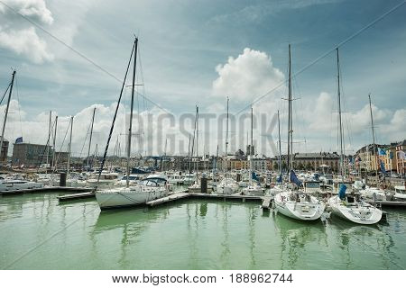 Yachts moored at quay port of Honfleur, France. Concepts of success, leisure, holiday, rich, tourism, luxury, lifestyle. Sunny Summer, blue sky.