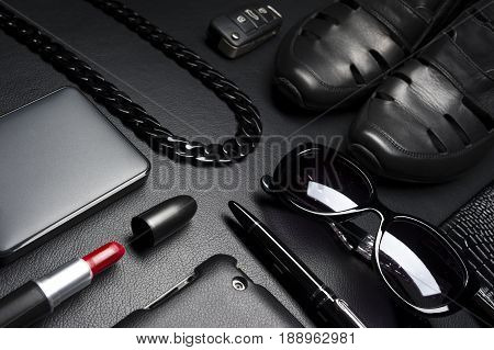 Woman accessories in business style, red lipstick, gadgets, jewelry, car key, eyewear, shoes, and other luxury businesswoman attributes on leather black background, fashion industry, selective focus
