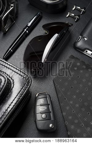Man accessories in business style, eyewear, clothes, gadgets, jewelry and other luxury businessman attributes on leather black background, fashion industry, selective focus