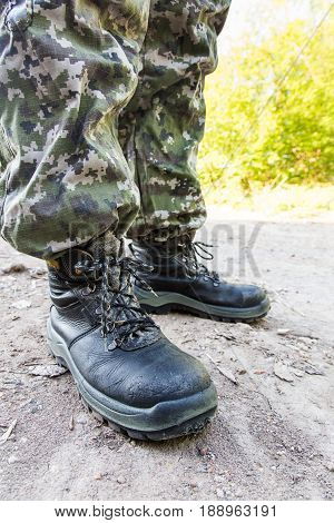 Body Parts. Legs In Camouflage Pants And Military Boots