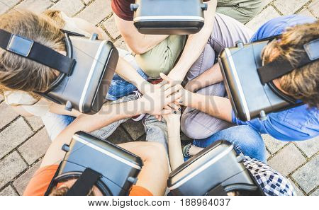 Top view of friends group playing on vr glasses with hands stacking - Virtual reality and wearable tech concept with young people having fun together with headset goggles - Digital generation trends