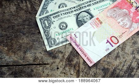 Us dollars and Malaysian ringgit currency on the wood table