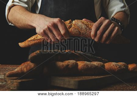 Baker's hands break the baguette