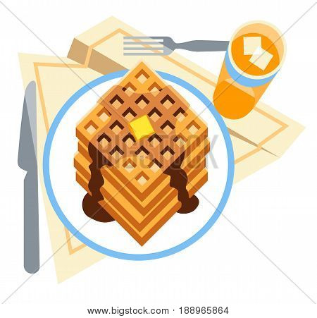 A tasty breakfast of waffles with butter and syrup, served with a glass of chilled juice.