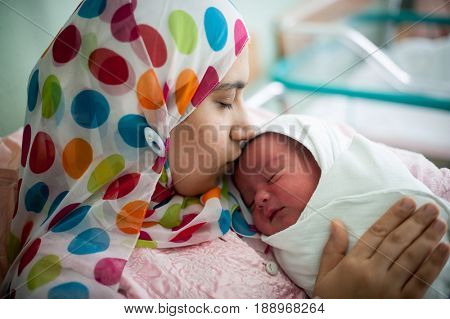 Arabic Muslim mother carrying her child in hospital bed immediately after delivery