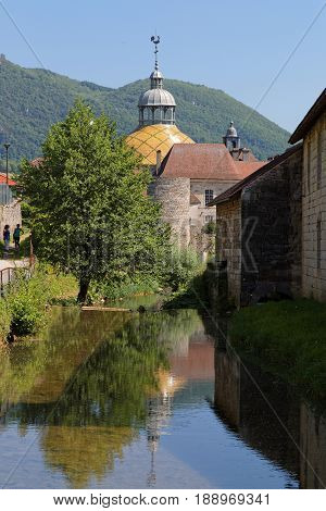 River behind the saltworks and City Hall coupole in Salins-Les-Bains Jura France. poster