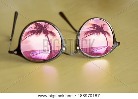 Digital nomad's sun glasses with palm tree and boat reflection on wood table