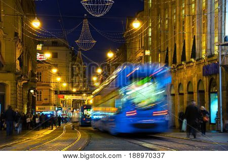 Zagreb, Croatia. Famous motion blurred blue Tram in the center of Zagreb, Croatia with local people at night. Illuminated historical buildings, cafes, restaurants and shops