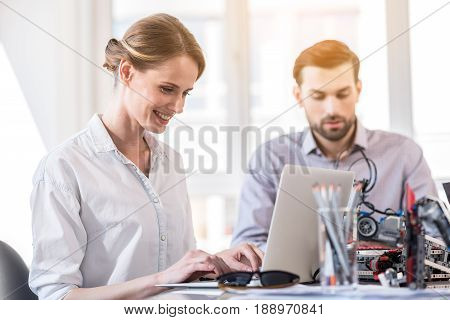Involved in work. Selective focus on joyful charming lady typing on laptop with smile while sitting at table. Young handsome bearded man working in the background