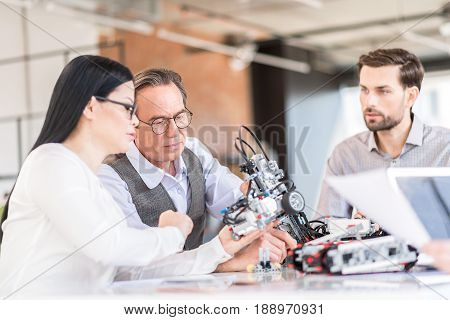 Our tech project. Attentive concentrated workers sitting at table and holding robot while expressing interest. Selective focus on senior man in glasses looking at mechanism intently