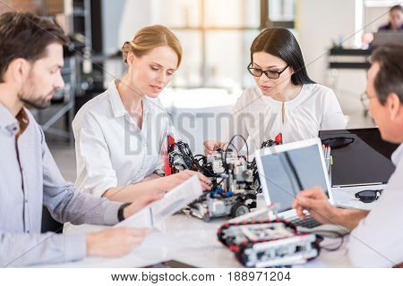 Time for new technologies. Group of inventors are working in office. Selective focus on two charming ladies are testing robots attentively