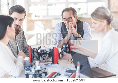 Process of discussion. Positive group of engineers are sitting around table with robot and listening their colleague woman. Focus on senior man wearing glasses