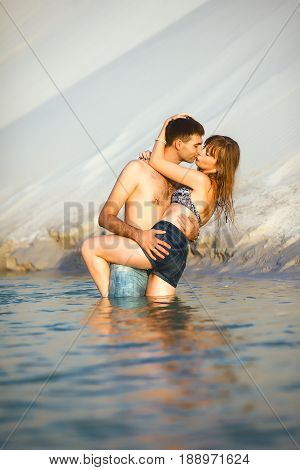 Beach lovers on romantic travel honeymoon vacation summer holidays romance. Young joyful girl and man kissing and embracing on water