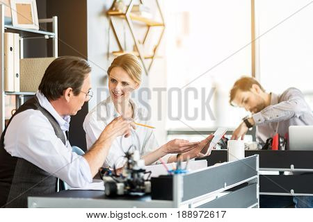 Great minds getting together. Confident senior man is pointing tablet while sitting together with his colleagues in office. Focus on charming woman holding gadget with smile
