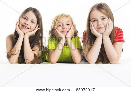 Three happy children laying down, isolated on white background