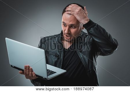 Portrait of young handsome man using laptop, wearing black leather jacket. Studio shot. Emotions