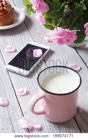 A cup of milk phone and dogrose on the white wooden table