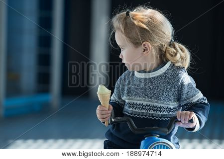 Baby Or Small Boy Eating Ice Cream On Toy Bike