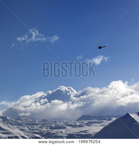 Helicopter Above Snowy Plateau And Sunny Sky