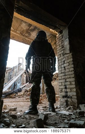 Silhouette of a soldier standing in the aisle of a ruined building