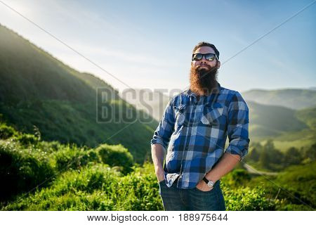 bearded guy with sunglasses and blue flannel posing in front of grassy green hills in california