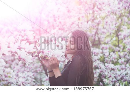 Adorable Girl With Brunette, Long Hair Enjoying Magnolia Flower Blossom