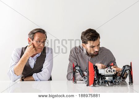 Not believing in result. Portrait of professional engineers are sitting at table. Young serious man is testing robot undistracted by his colleague which is looking at him incredulously. Isolated