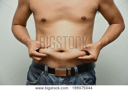 Asian fat man has cholesterol . He shows excess fat of the tummy. By hands use the squeeze at the his tummy. / Photo concept: fat belly obesity cellulite
