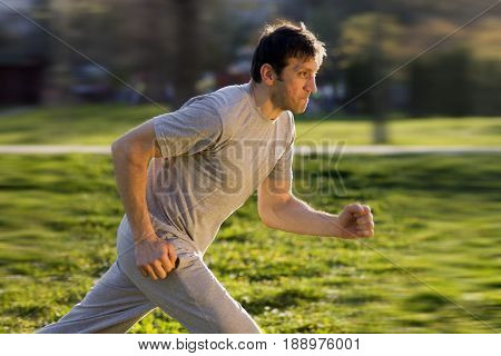 The man is running outdoors at the park.