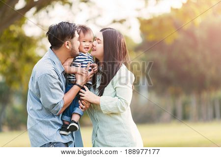 Happy mother and father kissing his little son in park