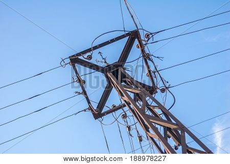 vintage electric pole with wires in a sunny day against the blue sky