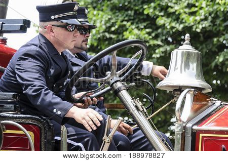 Bristol Rhode Island USA - July 4 2011: Firefighters aboard antique fire engine at Independence Day parade in Bristol Rhode Island