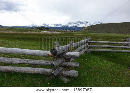 A crooked-rail fence in a meadow at Stanley, Idaho with the Sawtooth Mountains in the background.