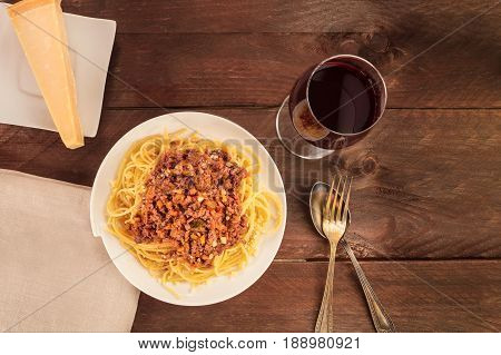An overhead photo of a plate of spaghetti Bolognese, with meat and tomato sauce, with a glass of red wine, a slice of Parmesan cheese, and a place for text