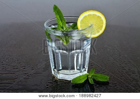 Fresh mint. Water in glass. Lemon and mint. Refreshing drink. Detoxification cure. Drops of water.
