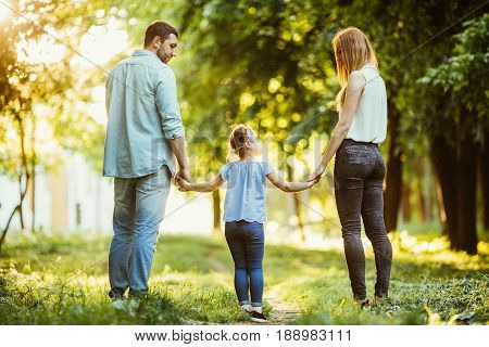 Happy Family In The Park. Mom, Dad And Baby Happy Walk At Sunset. The Concept Of A Happy Family. Par