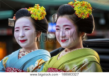 KYOTO, JAPAN - NOVEMBER 11, 2016: Maiko women, apprentice geisha on the street parade in Kyoto, Japan. Kyoto was formerly the Imperial capital of Japan for more than one thousand years