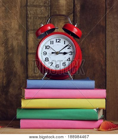 Stack of books in colorful covers autumn leaves and red alarm clock on the table. Back to school. The teacher's day. The first of September.
