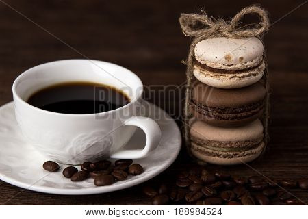 Set of coffee macaroons with a cup of coffee on dark wooden background. Cream macaroons
