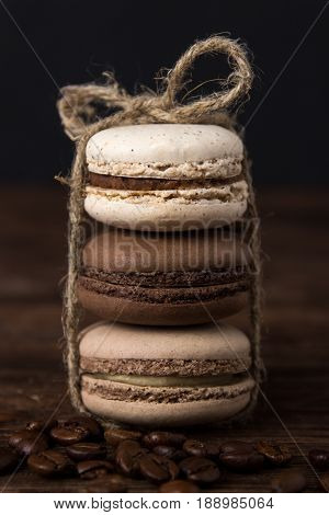 Set of coffee macaroons on dark wooden background. Cream macaroons