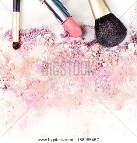 Makeup brushes and lipstick on a white background, with traces of powder and blush on it. A square template for a makeup artist's business card or flyer design, with copy space