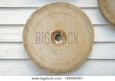 vintage grinding stone hanging on a house wall