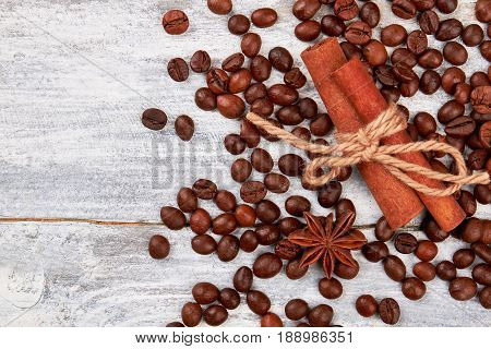 Coffee grain on wooden background. Cinnamon and badian on table. Coffee pleases the eye.